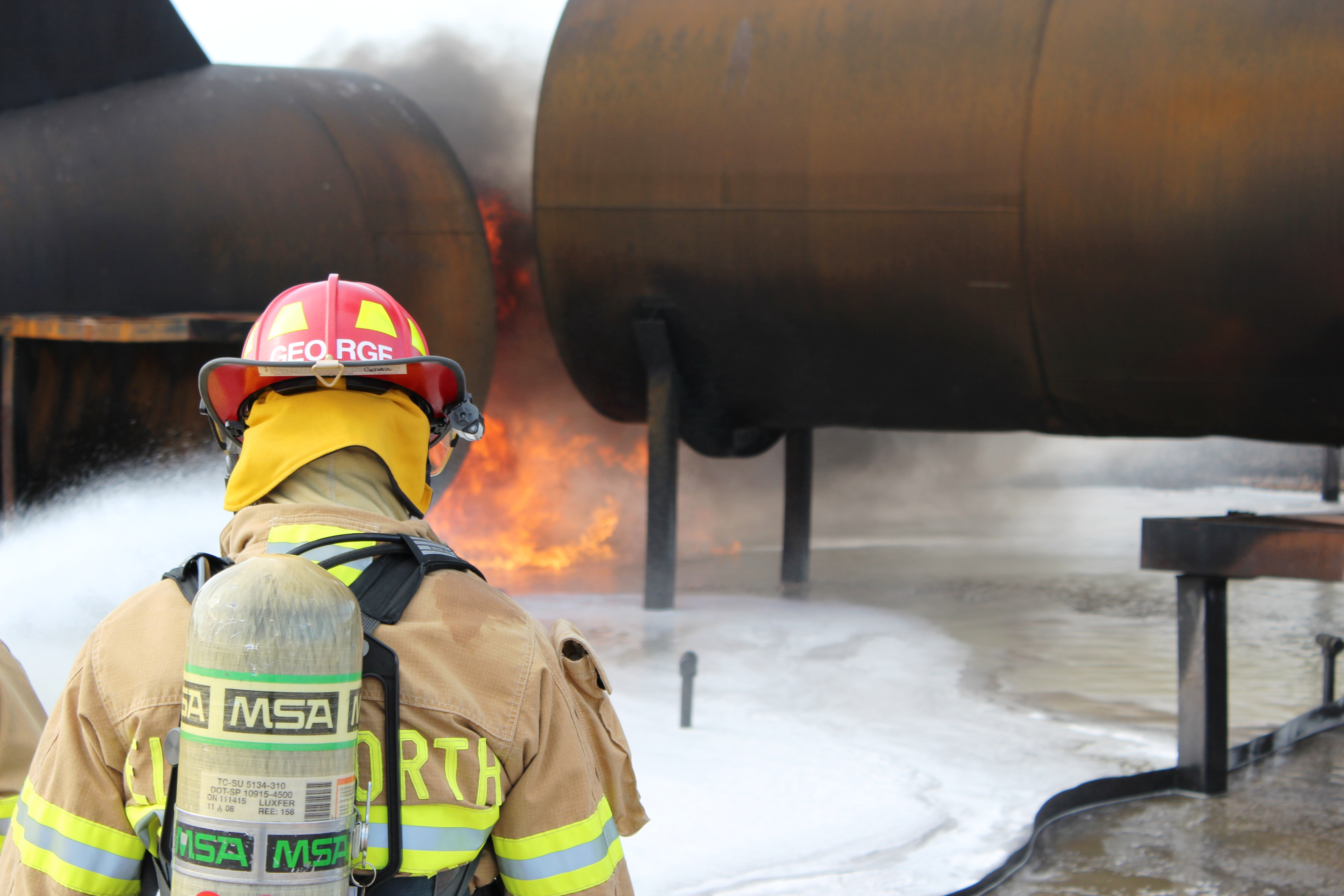 Firefighters putting out a fire at an aircraft firefighting training site